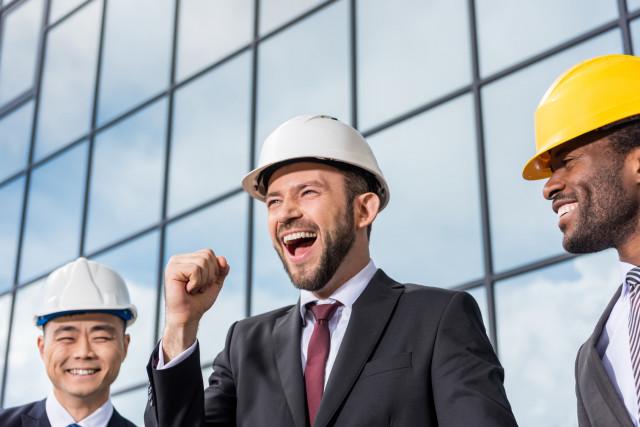 happy-professionals-with-hardhat_Fotolia_153425782_M
